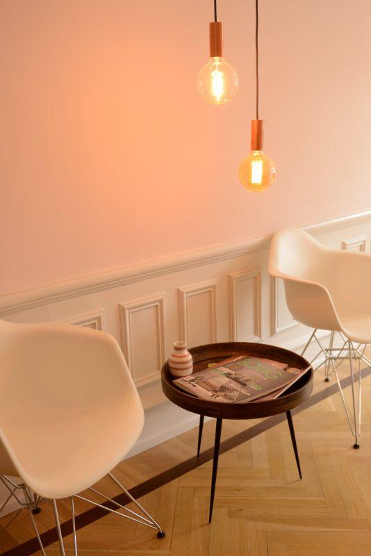 lyserød væg med hvide stole, el-pære og rundt bord