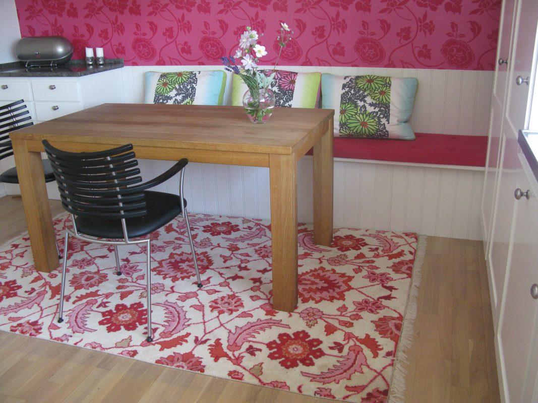 Lyserødt køkkenhjørne med træbord og bænk